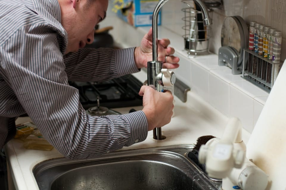 A man tries to fix a kitchen sink.