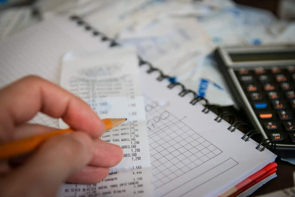 A person is seen pouring over bills and paperwork.